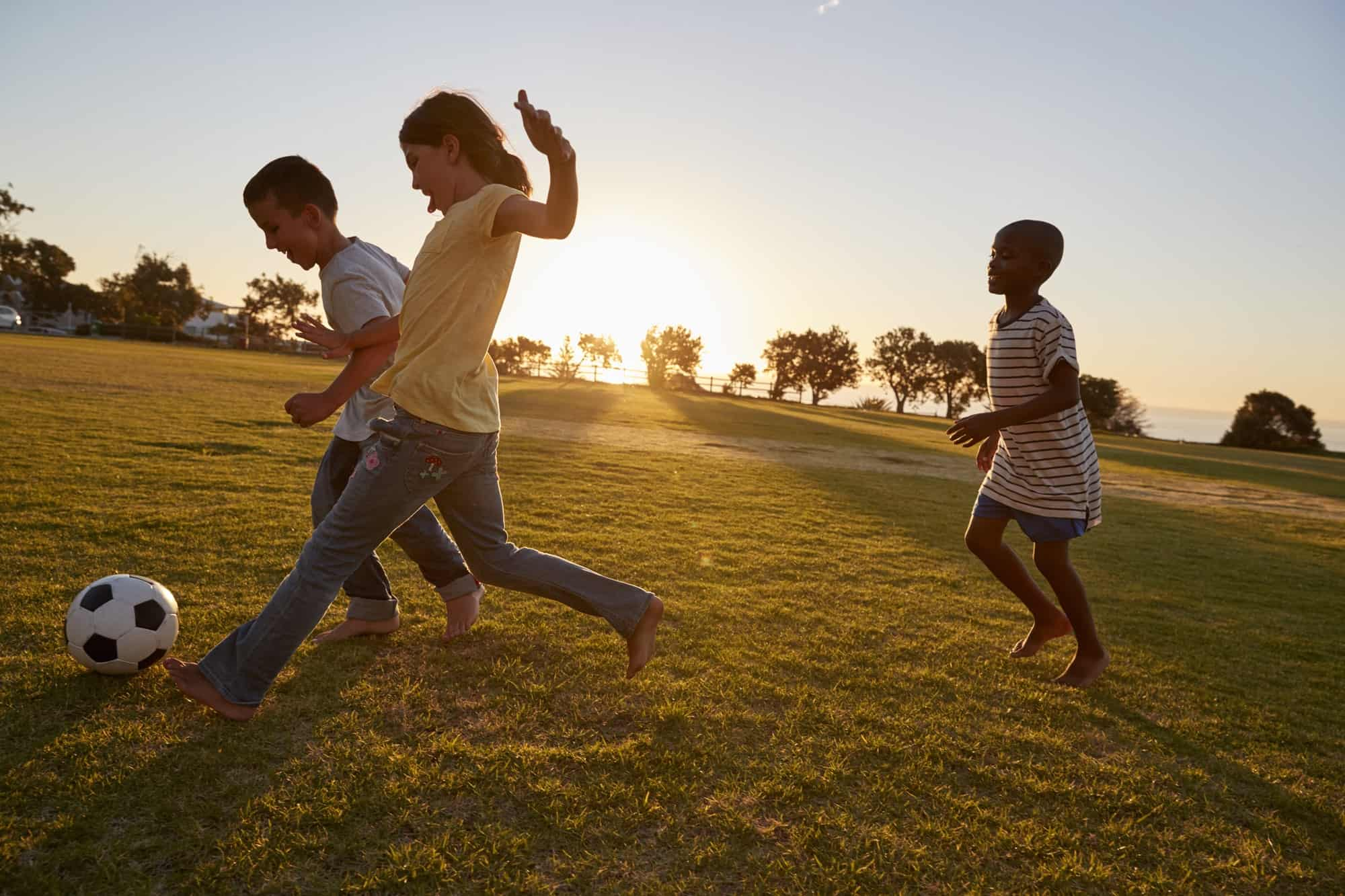 Three children playing football in a field